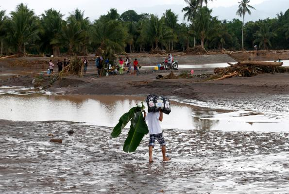 At least 100 dead and dozens missing as tropical storm batters Philippines