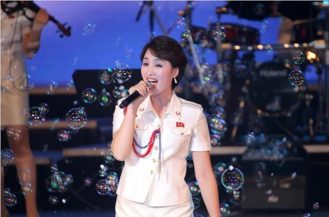 """A singer in the 10-member North Korean girl band Moranbong performed in concert in 2014. The band's lyrics are like a """"textbook for life,"""" claimed North Korea's state media. Photo by Yonhap"""